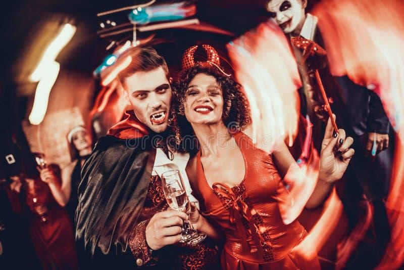 Pares felices jovenes en trajes en el partido de Halloween imágenes de archivo libres de regalías