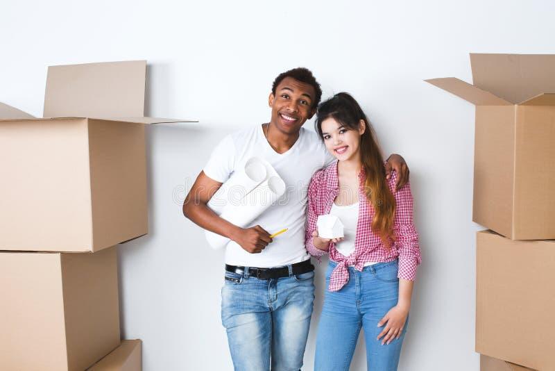 Pares felices jovenes en una nueva casa Piense hacia fuera el interior fotografía de archivo