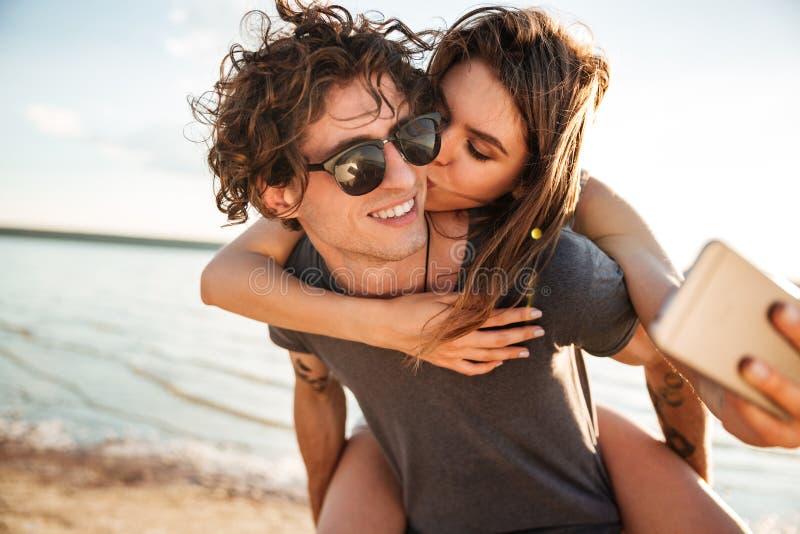 Pares felices jovenes que besan y que hacen el selfie en la playa fotografía de archivo