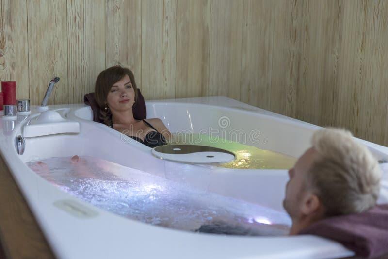 Pares felices jovenes que disfrutan del baño en el Jacuzzi - par de amantes en una piscina del Jacuzzi fotos de archivo libres de regalías