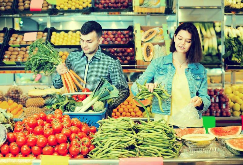 Pares felices jovenes que eligen verduras en tienda de ultramarinos fotos de archivo