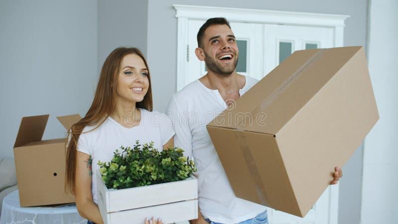 Pares felices jovenes que hablan mientras que se coloca en su nueva casa imagen de archivo