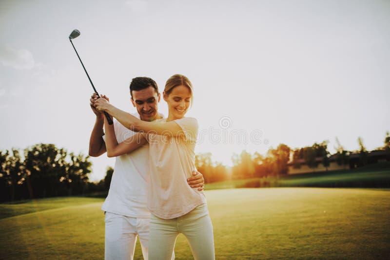 Pares felices jovenes que juegan a golf en campo en verano fotos de archivo libres de regalías