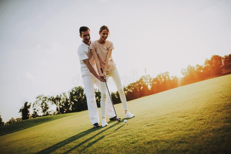 Pares felices jovenes que juegan a golf en campo en verano imagen de archivo