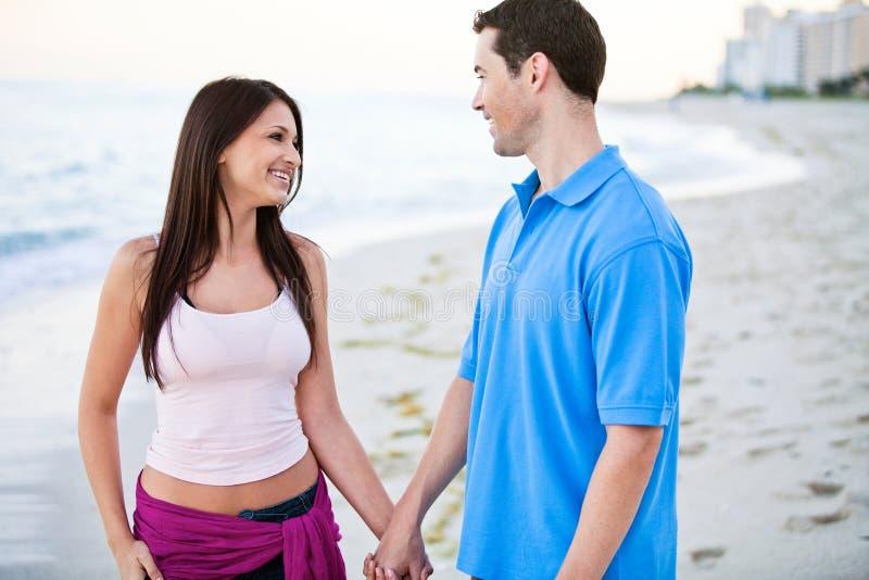 Pares felices jovenes que llevan a cabo las manos en la playa fotos de archivo