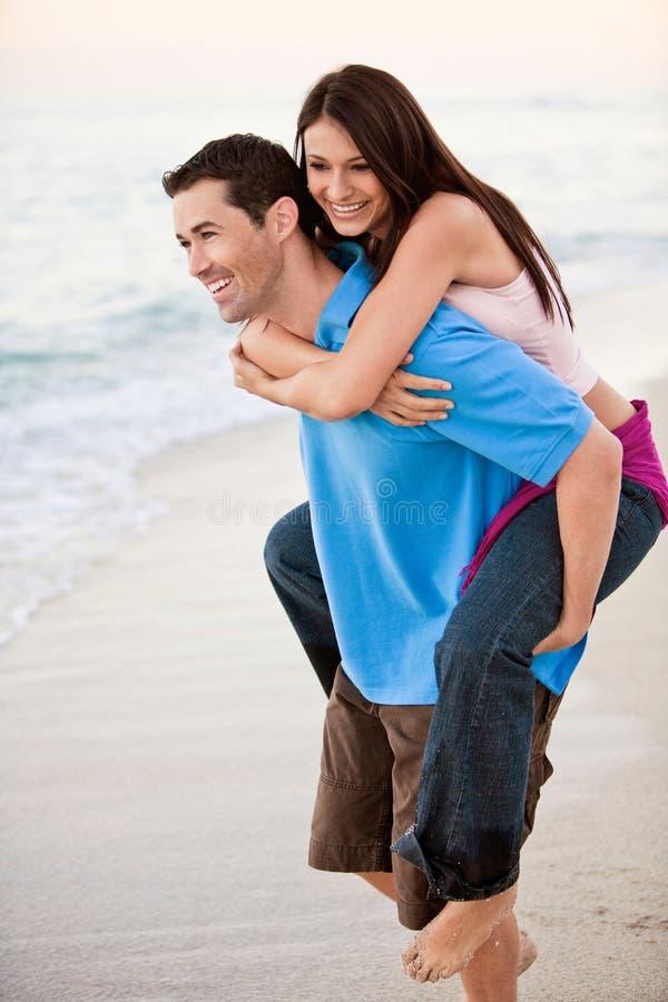 Pares felices jovenes que llevan a cabo las manos en la playa imagenes de archivo