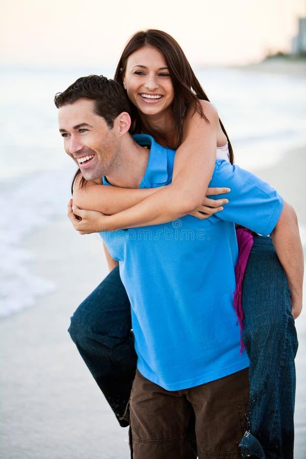 Pares felices jovenes que llevan a cabo las manos en la playa foto de archivo libre de regalías