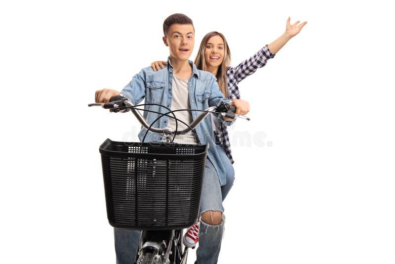 Pares felices jovenes que montan en una bicicleta imágenes de archivo libres de regalías