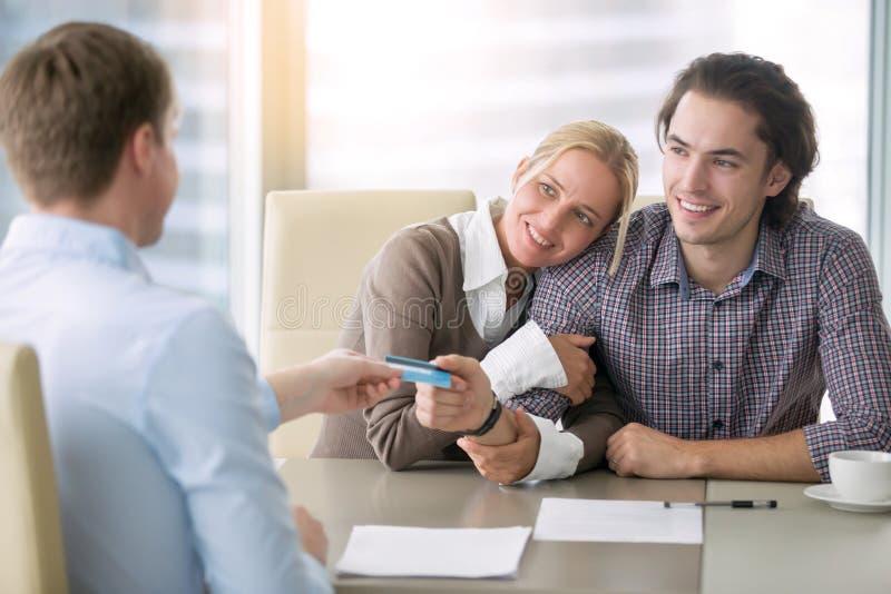 Pares felices jovenes que pagan con la tarjeta foto de archivo libre de regalías