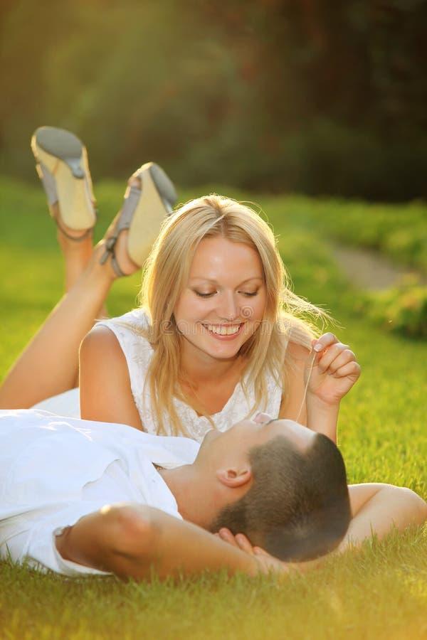 Pares felices jovenes que se acuestan en hierba en el sol foto de archivo