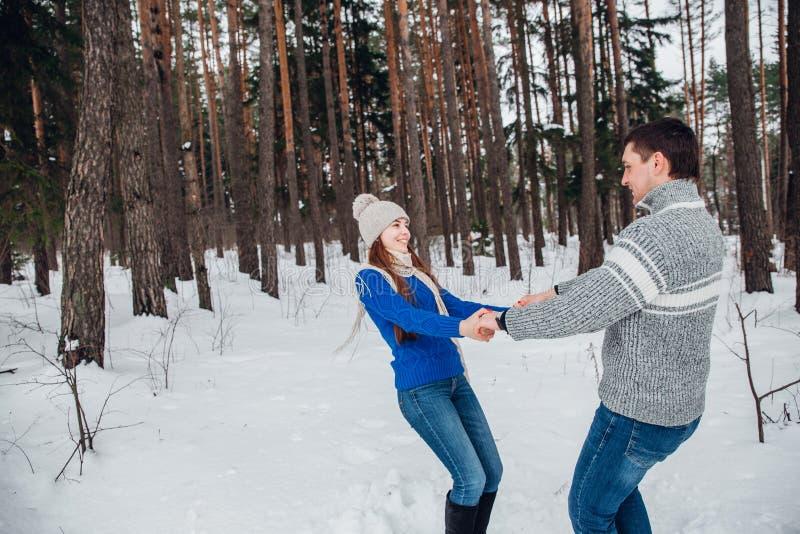 Pares felices jovenes que se divierten en parque del invierno imágenes de archivo libres de regalías