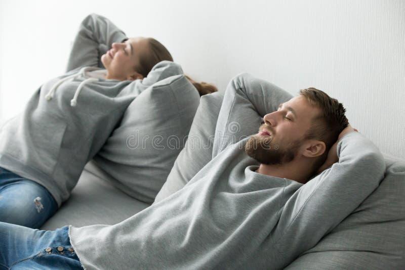 Pares felices jovenes que se relajan en el sofá cómodo junto en el hom fotografía de archivo