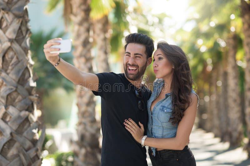 Pares felices jovenes que se toman la foto junto imagen de archivo libre de regalías