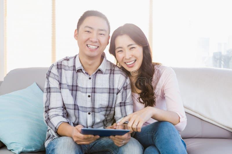 Pares felices jovenes que sostienen la tableta digital fotografía de archivo
