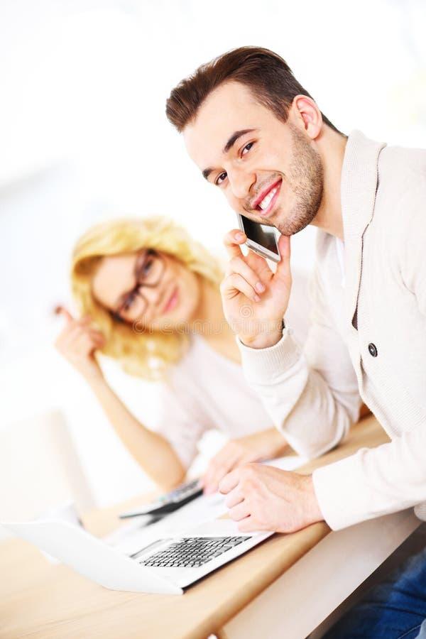 Pares felices jovenes que trabajan en documentos en casa foto de archivo libre de regalías