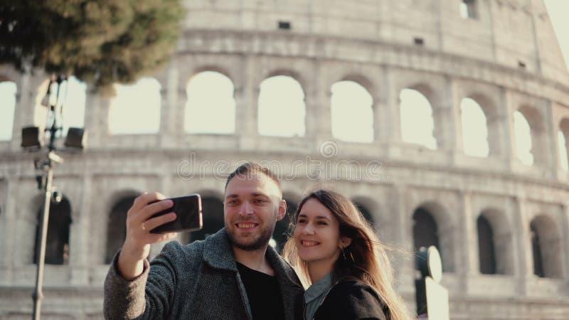 Pares felices jovenes que viajan en Roma, Italia Hombre y mujer que toman la foto del selfie en smartphone cerca del Colosseum fotografía de archivo