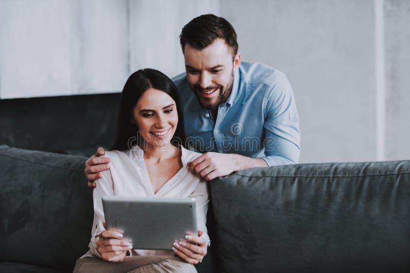 Pares felices jovenes usando el dispositivo de la tableta en casa imágenes de archivo libres de regalías