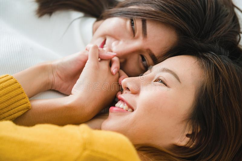 Pares felices lesbianos asiáticos jovenes hermosos de las mujeres LGBT que abrazan y que sonríen mientras que miente junto en cam imagenes de archivo