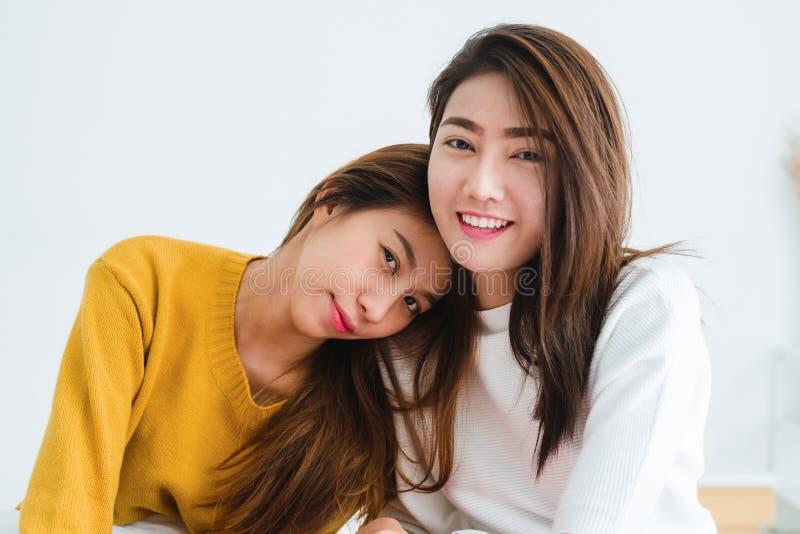 Pares felices lesbianos asiáticos jovenes hermosos de las mujeres LGBT que se sientan en la cama que abraza y que sonríe junto en fotos de archivo