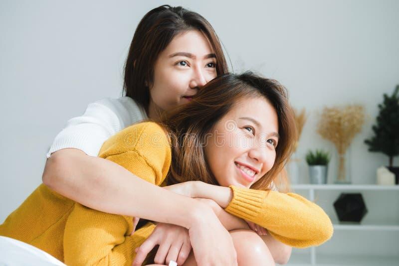 Pares felices lesbianos asiáticos jovenes hermosos de las mujeres LGBT que se sientan en la cama que abraza y que sonríe junto en fotografía de archivo libre de regalías