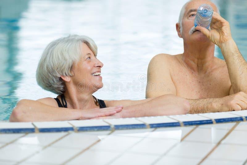 Pares felices mayores en piscina fotos de archivo