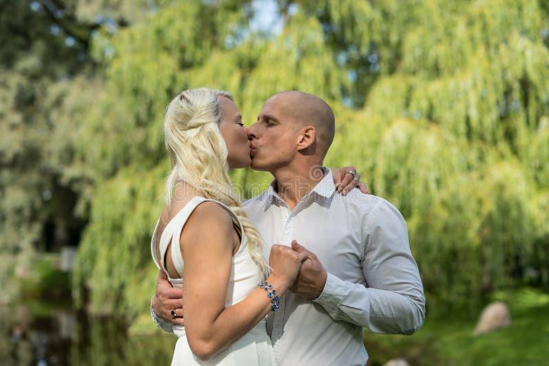Pares felices Novio que besa y que abraza a la novia Hombre y mujer en amor imágenes de archivo libres de regalías