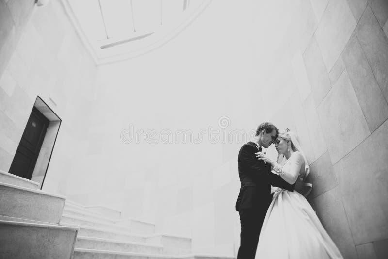 Pares felices preciosos de la boda, novia con el vestido blanco largo que presenta en ciudad hermosa imagenes de archivo