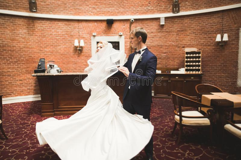 Pares felices preciosos de la boda, novia con el vestido blanco largo que presenta en ciudad hermosa fotografía de archivo libre de regalías