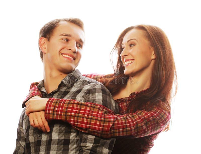Pares felices preciosos que abrazan sobre fondo gris fotos de archivo