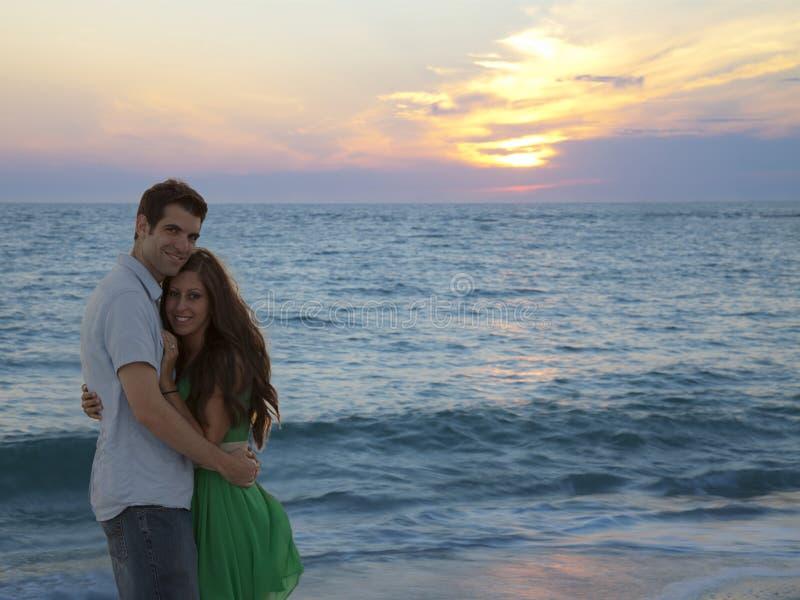 Pares felices que abrazan durante la playa de la puesta del sol fotografía de archivo