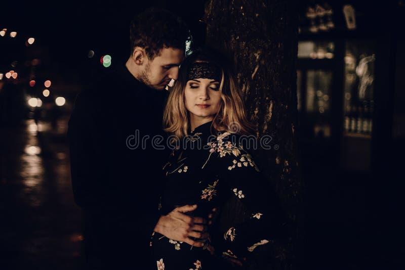 Pares felices que abrazan en la calle en la noche, embrac hermoso del hombre imagen de archivo