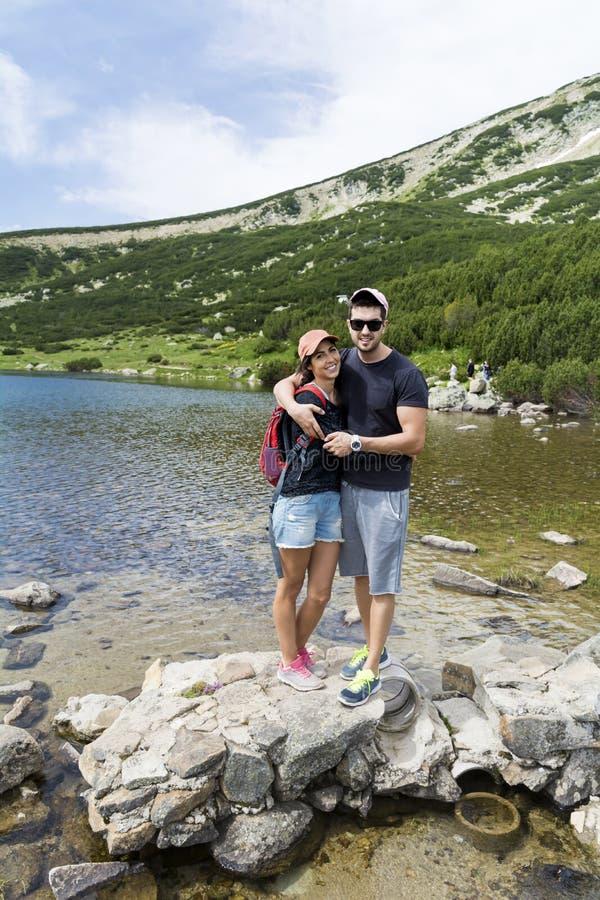 Pares felices que abrazan en la montaña de Pirin foto de archivo