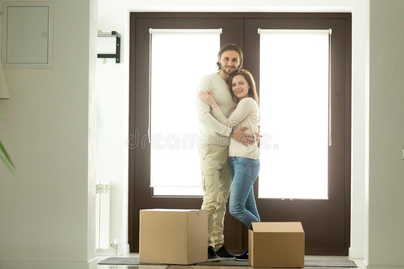 Pares felices que abrazan mirando la cámara que se traslada a nuevo hogar fotos de archivo libres de regalías