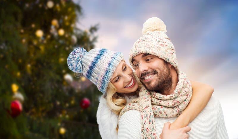 Pares felices que abrazan sobre el árbol de navidad imagen de archivo libre de regalías