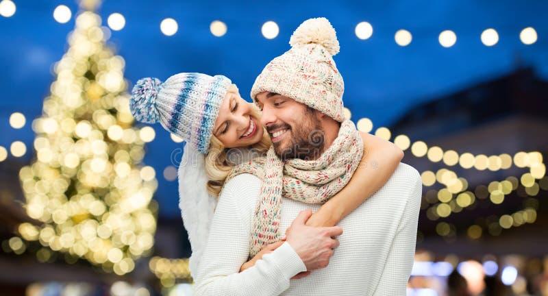 Pares felices que abrazan sobre luces del árbol de navidad imagen de archivo