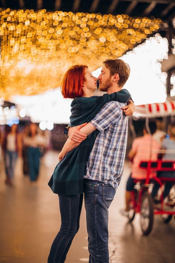 Pares felices que abrazan y que besan por la tarde en las guirnaldas ligeras fotos de archivo