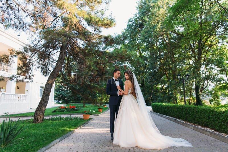 Pares felices que abrazan y que cuelgan hacia fuera en el parque La novia en un traje negro con una corbata de lazo y una novia e foto de archivo libre de regalías