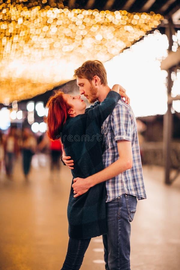 Pares felices que abrazan y que besan por la tarde en las guirnaldas ligeras fotos de archivo libres de regalías