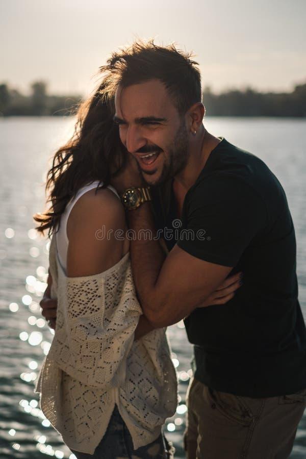 Pares felices que abrazan y que ríen por el río en puesta del sol foto de archivo