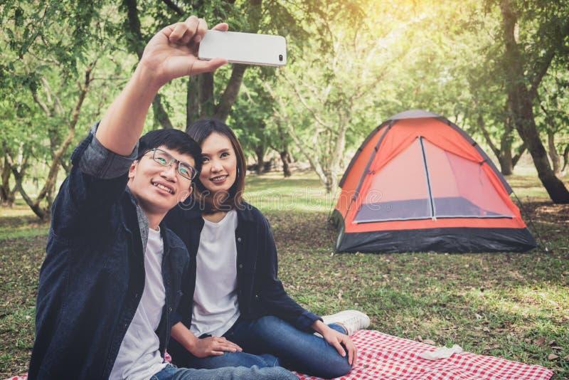 Pares felices que acampan en la naturaleza, tomando un selfie tirado de smil imagenes de archivo