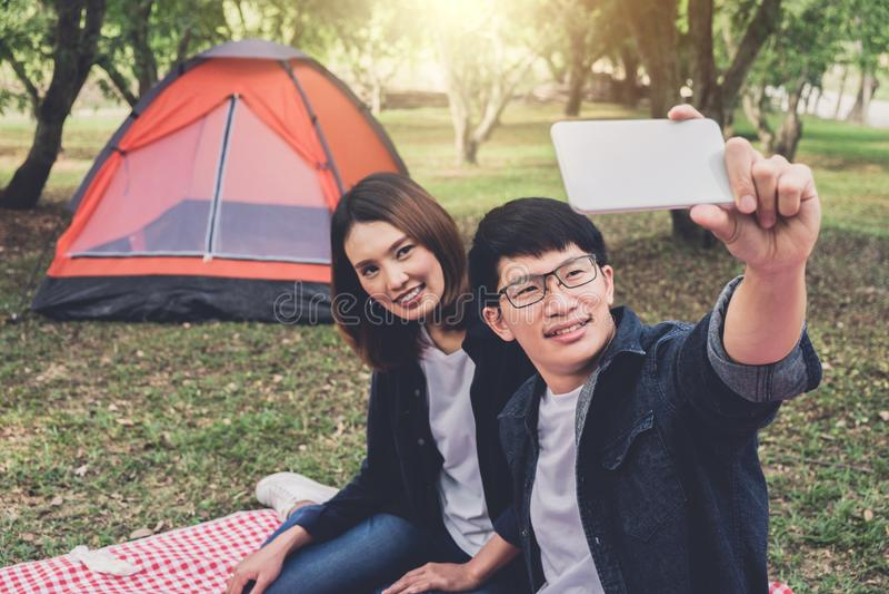 Pares felices que acampan en la naturaleza, tomando un tiro del selfie de la sonrisa imagen de archivo