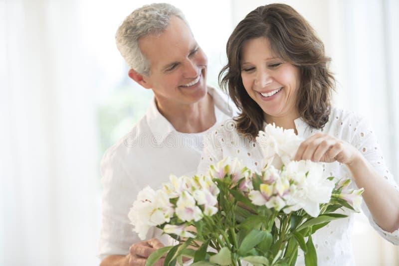 Pares felices que arreglan las flores imágenes de archivo libres de regalías