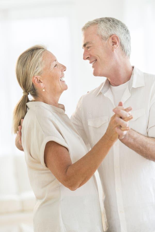 Pares felices que bailan en casa imágenes de archivo libres de regalías