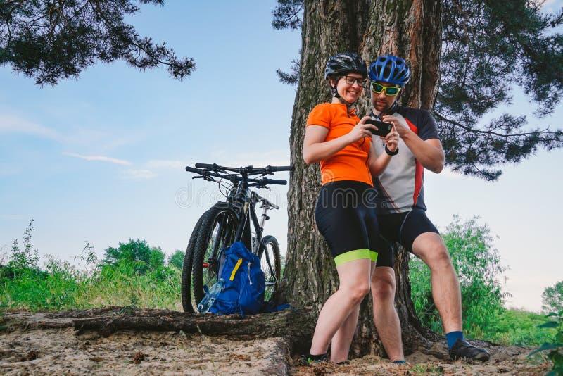 Pares felices que buscan en mapa en el destino del smartphone hombre y mujer en biking de montaña de los cascos que viaja sobre t imágenes de archivo libres de regalías