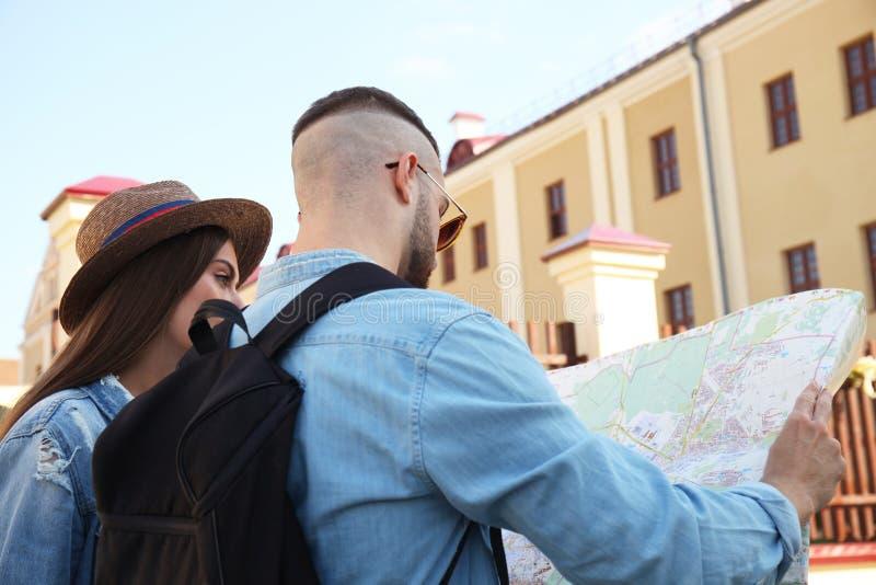 Pares felices que caminan al aire libre haciendo turismo y sosteniendo un mapa fotografía de archivo