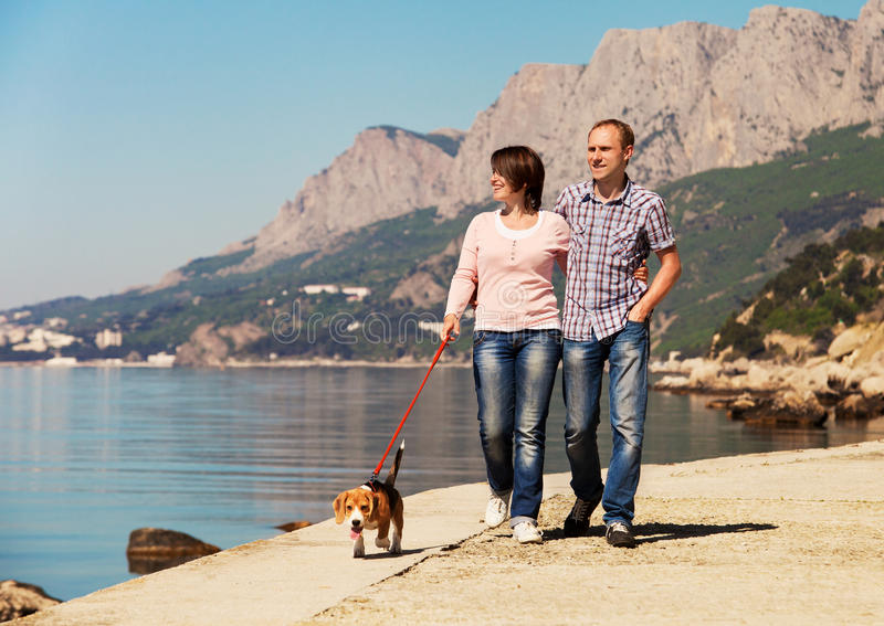Pares felices que caminan con el perrito en la costa imagen de archivo libre de regalías