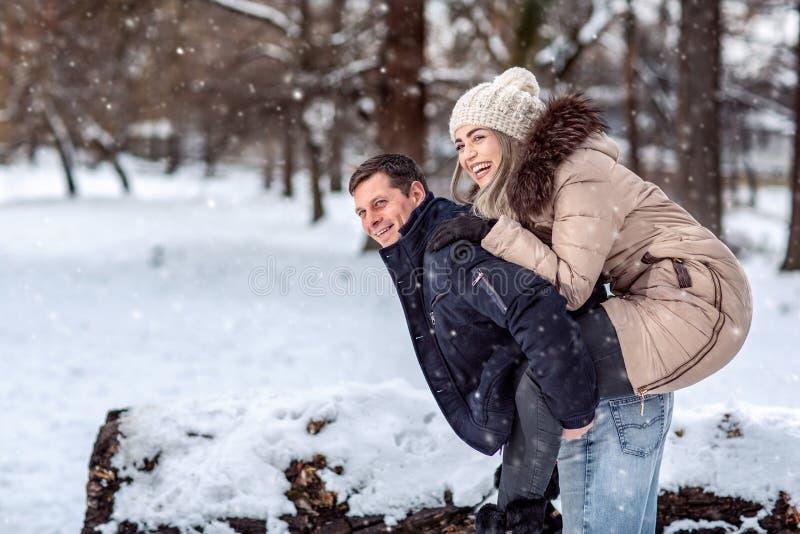 Pares felices que caminan en el bosque nevoso del invierno, pasando la Navidad fotos de archivo