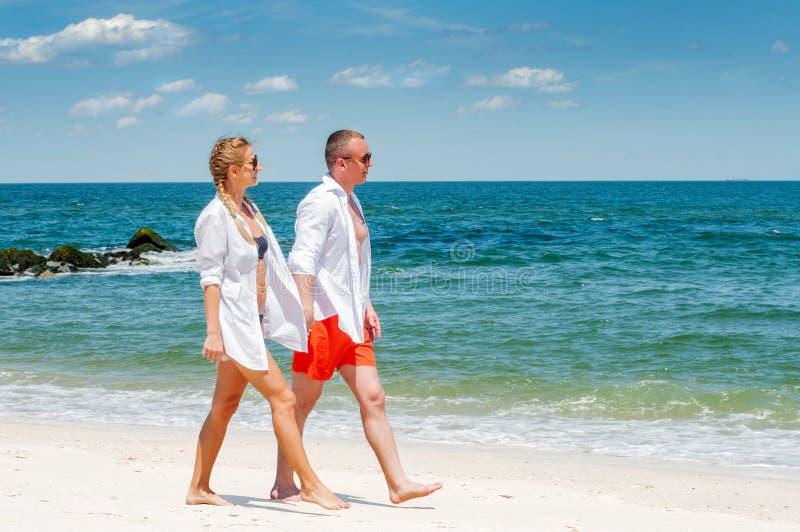 Pares felices que caminan en la playa, vacaciones románticas de la luna de miel del viaje foto de archivo