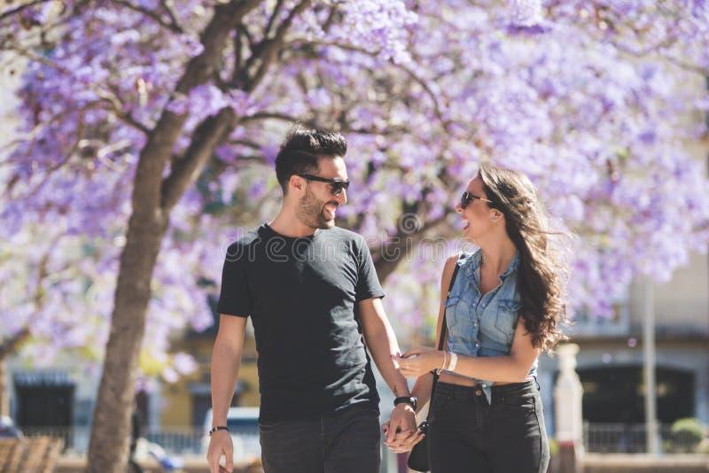 Pares felices que caminan junto de común acuerdo riendo foto de archivo libre de regalías