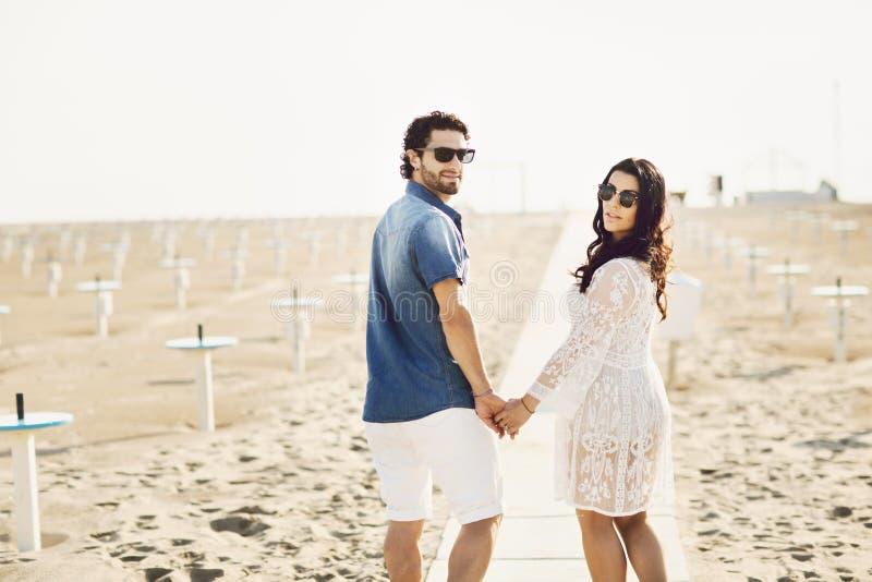 Pares felices que caminan a lo largo del mar, llevando a cabo las manos Muchacha en el vestido blanco, hombre en una camisa de lo imagen de archivo libre de regalías
